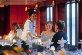 Happy couple being served dinner in an elegantly appointed ship's dining room.